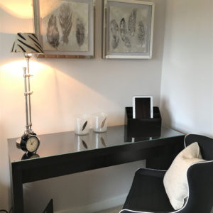 Black work office with elegant chair, black desk, decorative lamp, picture frames and decorative accessories