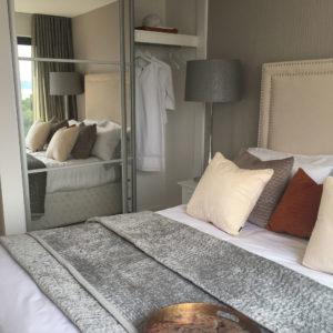 Modern bedroom with decorative cushions, wardrobe with a mirrored door, statement lighting and grey throw