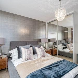 Open bedroom with grey bed, chandelier, wardrobe with mirrored door, statement lamps, velvet cushions and velvet throws