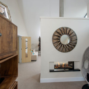 Modern fireplace with statement mirror, brown cabinet, beige carpet and white walls