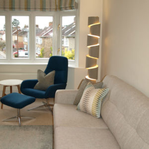 Beige sofa with statement lamp, navy blue armchair with footstool, decorative cushions and big windows