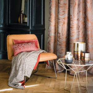 Chic orange chair with decorative red cushions, glass table with gold accents and gold accessories, with floral orange curtains