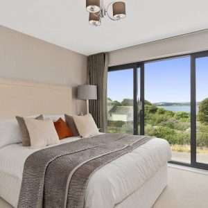 Open bedroom with decorative cushions, grey lamp, grey throw and big doors