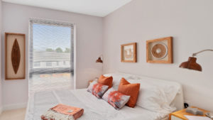 White bedroom with orange decorative cushions and picture frames, big window with blinds and statement lighting