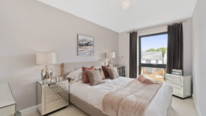 White bedroom with silver and blush pink accents, decorations and accessories, with a big window