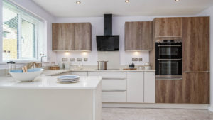 Clean open plan kitchen with white surfaces and spotlights