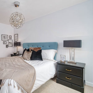 Blue bed with decorative throws, cushions, black bedside cabinet, decorative items, statement lighting and picture frames