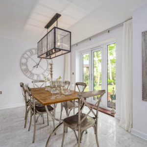 Wood dining table with metal chairs, statement lighting and big vintage clock