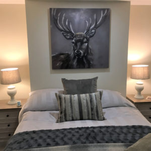 Bedroom with statement stag art on wall, cushions and lamps