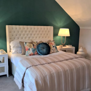 White bed with decorative floral, velvet cushions, green walls, statement lamp and decorative items