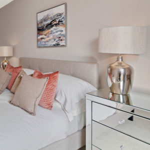 Bedroom with decorative cushions, mirrored bedside table, art on wall and statement lamps