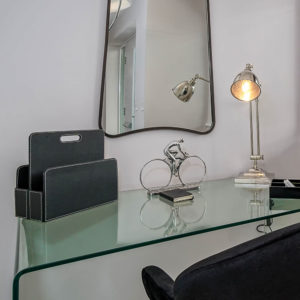 Workspace with glass desk, black chair, silver accessories and big statement mirror