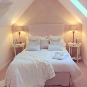 Pink and white bedroom with fluffy cushions, pink lamps, white bedside table and pink bed