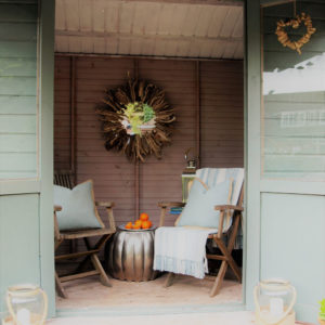 Outdoor garden shed with deckchairs, table, blue wooden doors and statement lamp