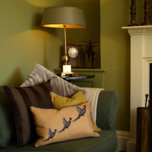 Green sofa with statement animal cushion, antique ornaments and white fireplace