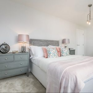 Grey bed with duck egg cabinet, pink lamp, pink throw, pink and blue cushions, decorative art and lamps