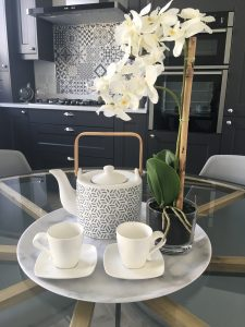 Glass dining table with gold accents, grey chairs, decorative ornaments and flowers in black kitchen with patterned wallpaper