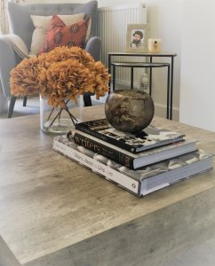 Marble table with decorative books, plants and grey chair with decorative cushions
