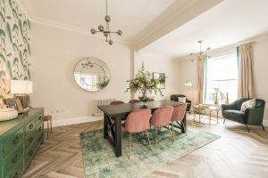 Black wooden dining table with velvet pink chairs, green sideboard, patterned wallpaper, statement mirror, velvet green armchairs and big green rug
