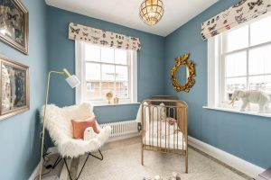 Luxury baby's nursery with gold metal crib, fluffy white armchair, blue walls, gold statement mirror, lamp and framed photos
