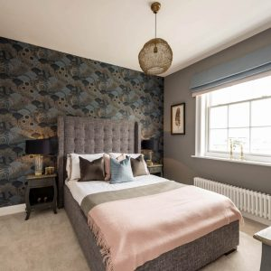 Grey fabric bed with green, grey and pink cushions and throws, art prints, bold patterned wallpaper and statement lighting