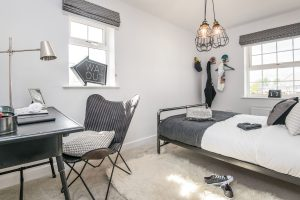 Modern teenager's bedroom with grey, white and black accents and decorations, fluffy white rug