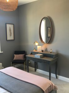 Dark grey vintage vanity table with statement mirror, small black chair and pink cushion