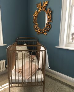 Gold baby's crib with dark blue walls, gold statement mirror, fluffy white cushion and pink throw