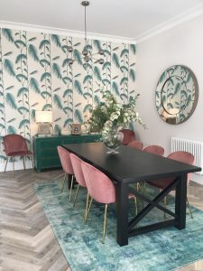 Black wooden dining table with velvet pink chairs, green sideboard, patterned wallpaper and statement mirror