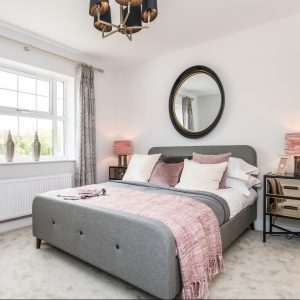 Grey fabric bed with blush velvet cushions, pink throw, statement mirror, gold and black bedside table, pink lamps and decorative ornaments