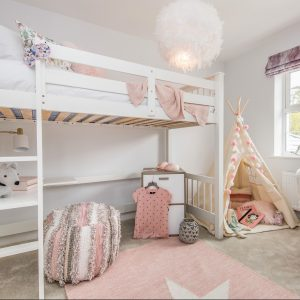 Young girl's bedroom with white loft bed, pink rug, pink throw, fluffy white light, beige tent and chic stool