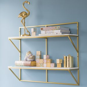 White and gold shelving with children's decorative items, gold flamingo and books