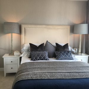 Beige bed with dark blue and grey cushions and throws, white bedside tables, grey lamps and decorative items