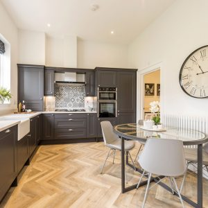 Dark grey kitchen with vintage statement clock, round dining table with glass top, modern grey chairs, and white walls