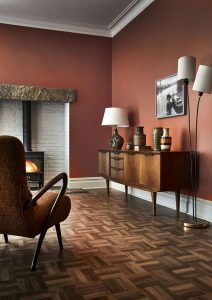 Dark wooden floors with wooden sideboard, statement lamps, decorative ornaments, big armchair, fireplace and red wallpaper