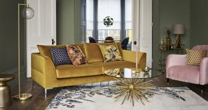 Gold velvet sofa and blush pink velvet chair with decorative cushions, lighting and accessories