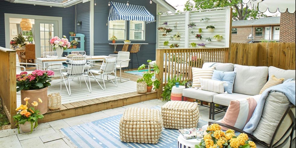 Outdoor garden space with dining table, sofas, cushions, throws, footstools, patio and rugs