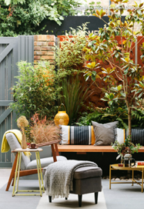 Outdoor garden space with sofas, armchairs, stools, throws and cushions