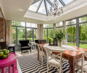 Sunroom with big wooden dining table, armchairs, chandelier, white chairs and pink cabinet