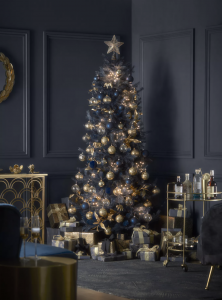 Navy blue Christmas tree with gold and blue decorations and baubles, with luxury drinks trolley and dark blue walls