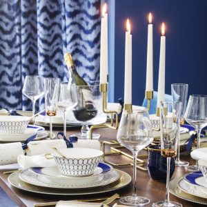 Blue and gold dining table spread with Christmas crackers and candles