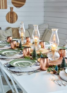 Dining table spread with candles and neutral colour scheme, copper cups and green plates