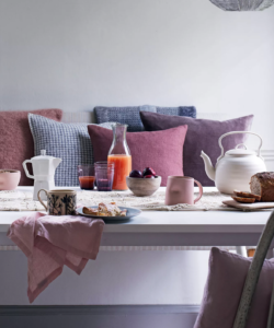 A dining table with purple cushions inspired by the Cottagcore interior design trend