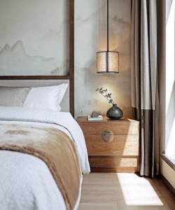 A Japanese inspired bedroom with white sheets, wooden bedside table and plant