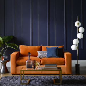 An orange sofa with cushions, navy painted walls and accessories including cushions and plants