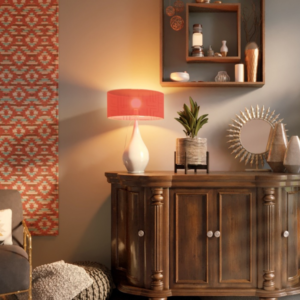 A wooden sideboard with accessories, including an orange lamp, plant, mirror and decorative items