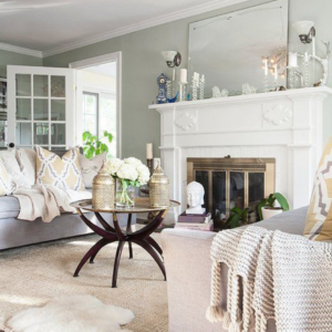 Living room with a neutral colour palette, throws, cushions and a big fireplace