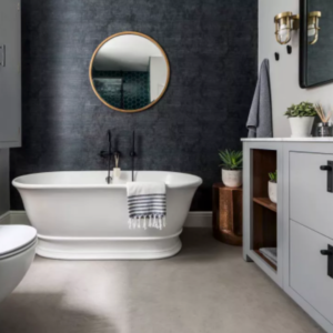 Bathroom with freestanding white bath with grey cabinets, a big mirror and various bathroom accessories