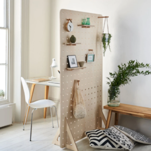 Small office space with a white chair, room divider with pegs, small wooden bench and plant