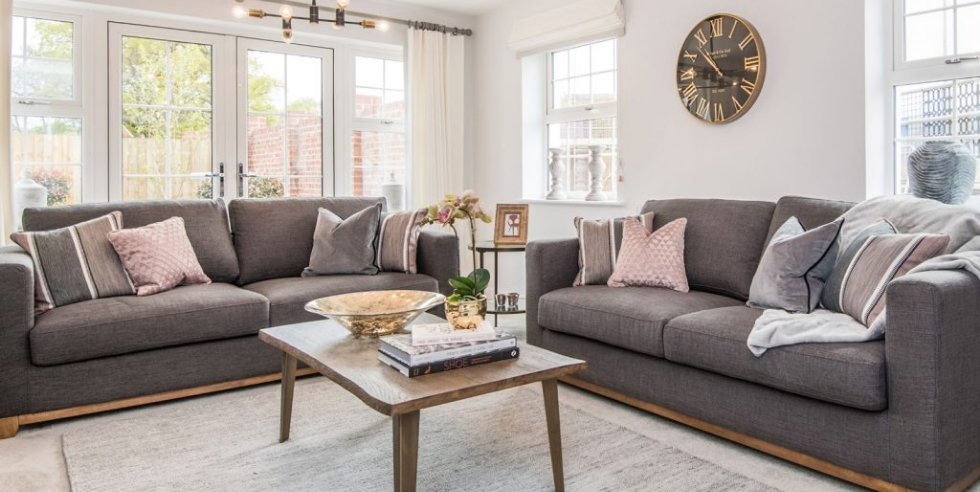 Living room with grey sofas, pink and grey cushions, statement lighting, big clock, wooden coffee table, decorative lamps and ornaments